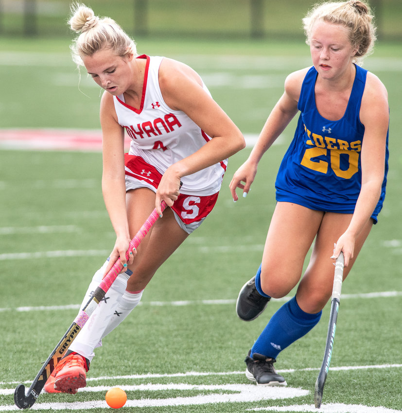 Smyrna's Reese Nacrelli, left, who scored three goals, brings the ball up the field against Caesar Rodney's Paige Hardee in the first quarter at Smyrna on Wednesday. The host Eagles won 6-1.
