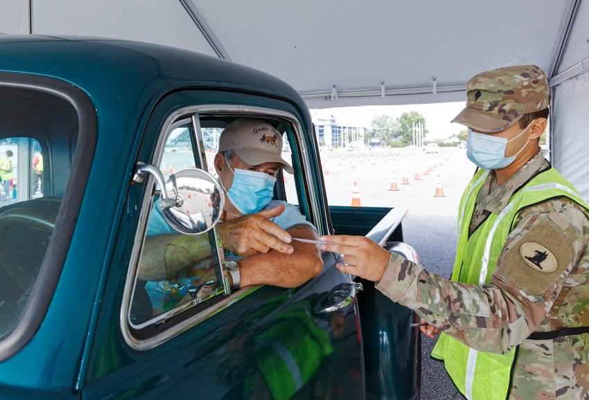 Delaware National Guard, Carpenter, Pablo Limon hands William Garlic his vaccination card after he received his COVID-19 booster shot during the COVID-19 vaccination clinic at the Dover International Speedway on Saturday.