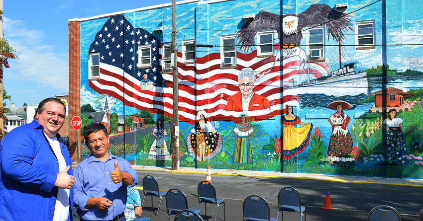 Craig Aleman, left, and Gilberto Rodriguez show Mr. Rodriguez's recently completed mural on the western wall of Mr. Aleman's two-story building along Pearl Street in downtown Seaford on Saturday.