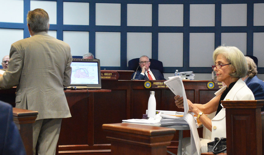 Michelle Forzley, among those appealing Sussex County Planning & Zoning Commission's approval of preliminary plans for Terrapin Island, looks at a map during Tuesday's appeal. At the podium is attorney Richard Forsten, representing the developer of the proposed Lewes community.