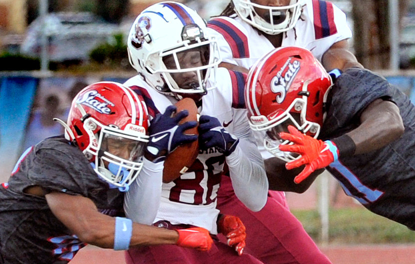 DSU's Denzel Bryant (left) and Dan Douglas converge on Richard Bailey of South Carolina State after a short pass reception Saturday.