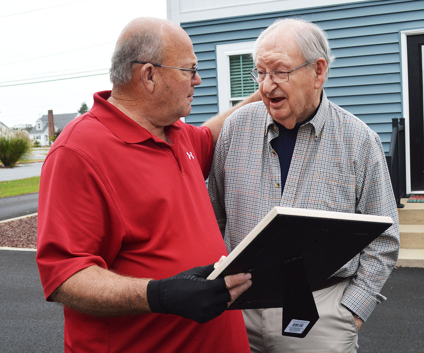 Georgetown Mayor Bill West, left, on behalf of the town, embraces Carlton Moore as he was presented a plaque in recognition of his impact in Georgetown and beyond.