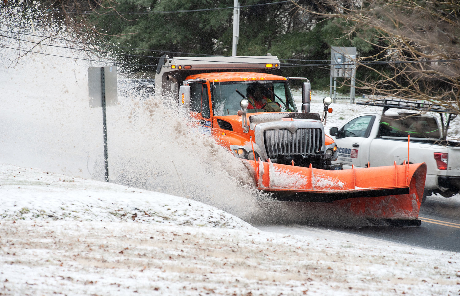 A DelDot snow plow aggressively pushes snow and ice off of Canterbury Road near Felton on Thursday. Sleet and snow is making driving dangerous in Kent County.