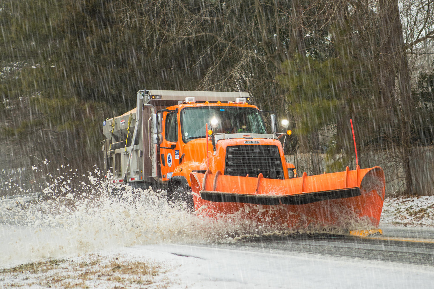 A DelDOT plow scrapes the road, putting down salt and sand in West Dover Thursday.  Submitted photo by Jerry Hull of Dover