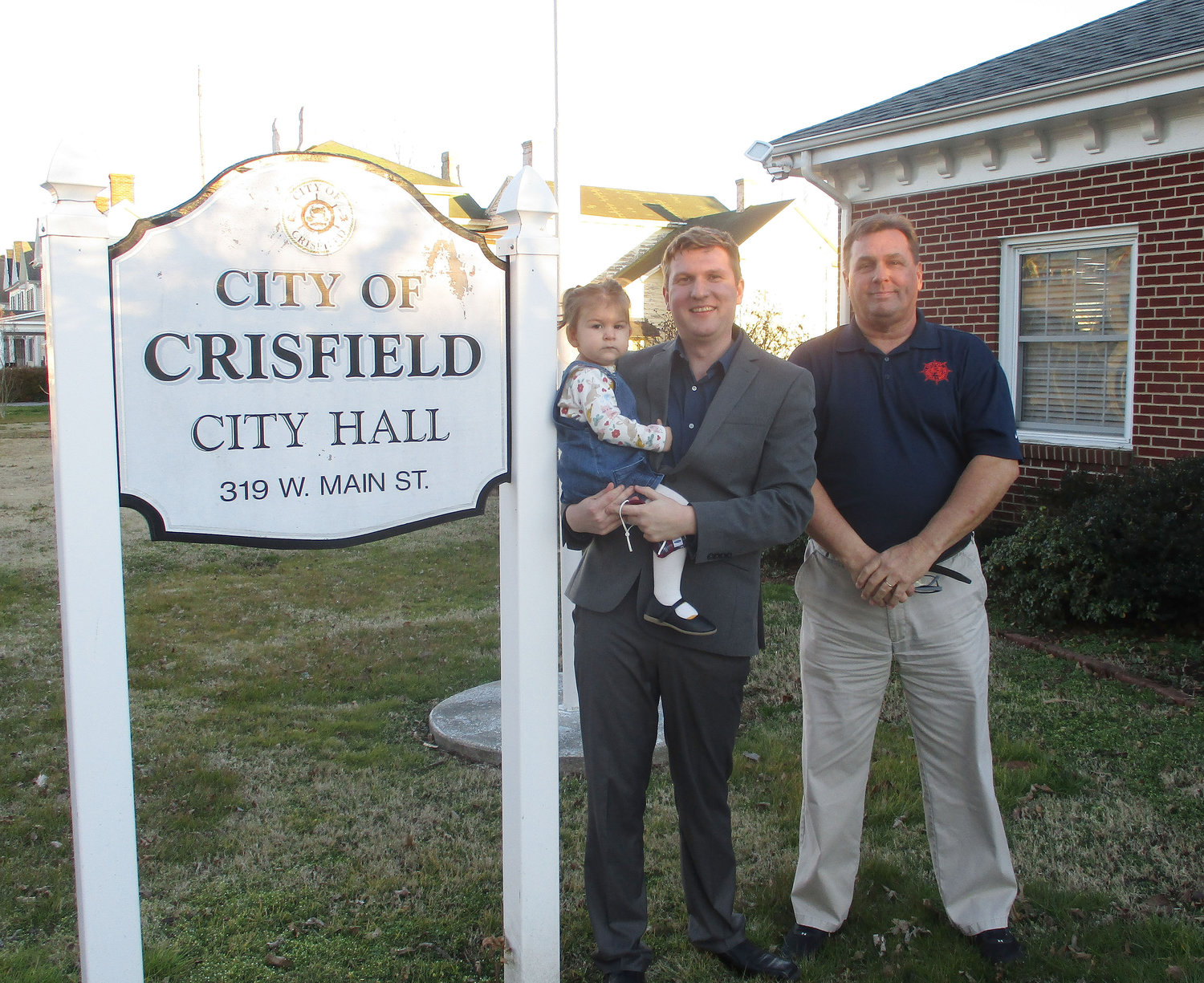 Crisfield City Councilman Casey Goldsborough and his daughter Amelia pose for photos with Mayor Barry Dize after Mr. Goldsborough was sworn-in to take the vacant council seat previously held by Nelson Sheppard.