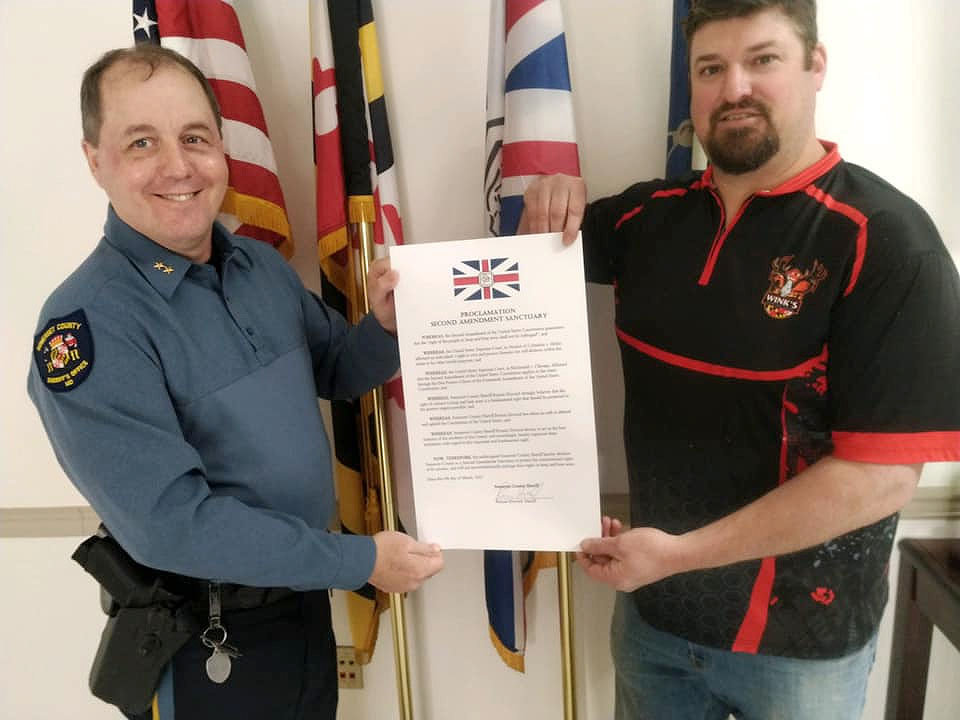 "Somerset County Sheriff Ronnie Howard and Princess Anne gun shop owner Jamie Wink hold a copy of the proclamation the sheriff signed making Somerset County a Second Amendment Sanctuary from the perspective of the Sheriff's Office. Now the County Commissioners are considering a formal resolution of their own. Mr. Wink has requested the commissioners declare the county a ""2A Sanctuary"" and last year they wrote a letter to the General Assembly delegation expressing their support for the right to bear arms."