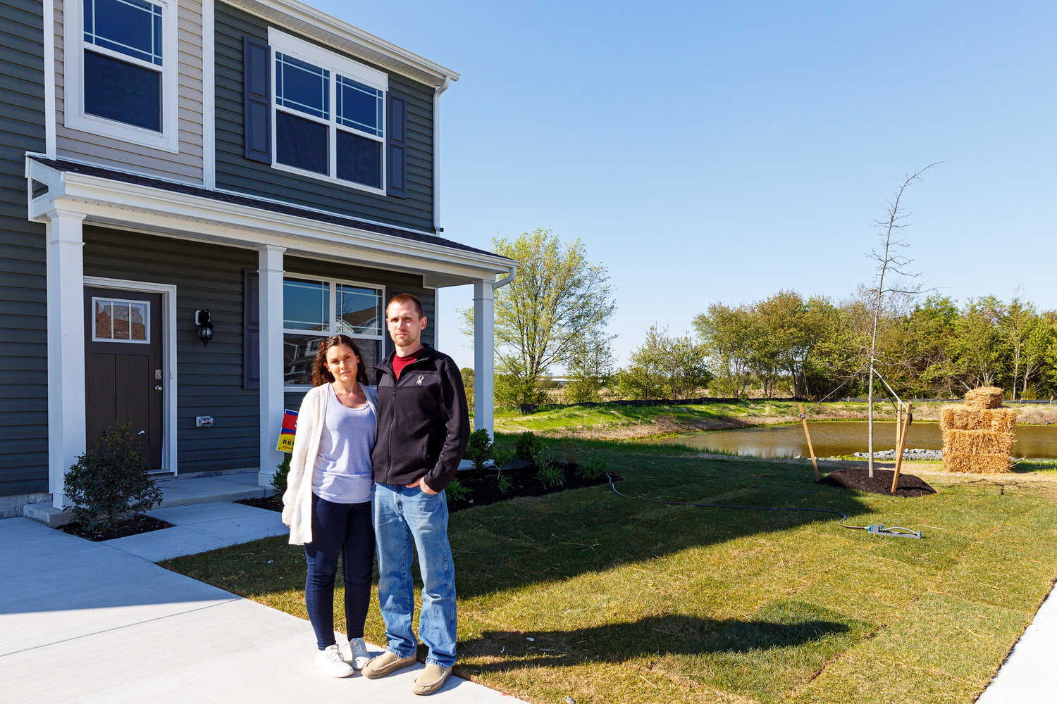 Caitlin and Brian Depelteau in front of their one-time home in Milford's West Shores. Since the developer is not repairing nearby retention ponds in the subdivision, nine families cannot move into their newly constructed homes.