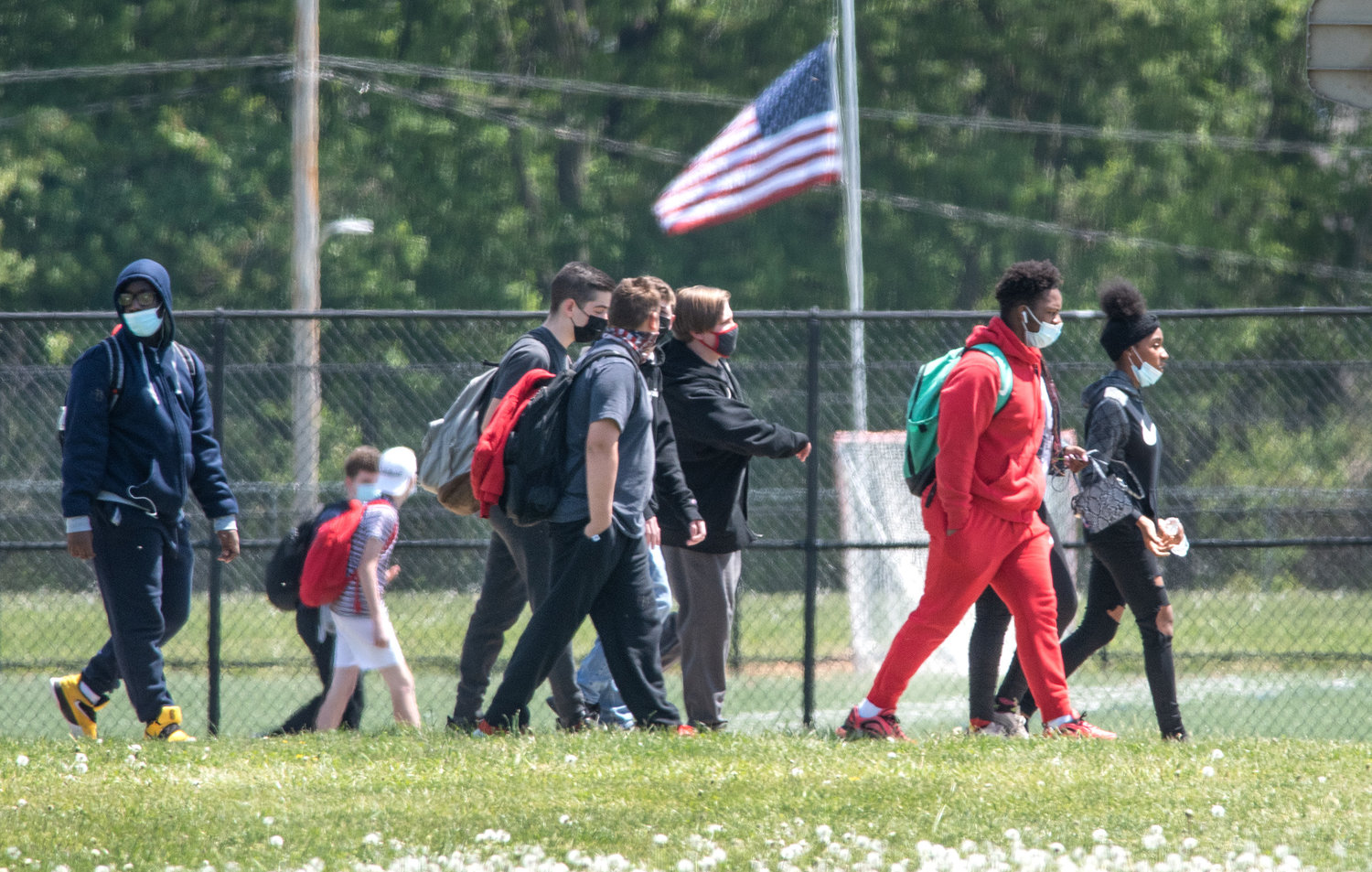 Smyrna Middle School students walk behind the school and head toward Smyrna High School to waiting busses and parents after a women was shot and died in the front of the Middle School on Tuesday morning.
