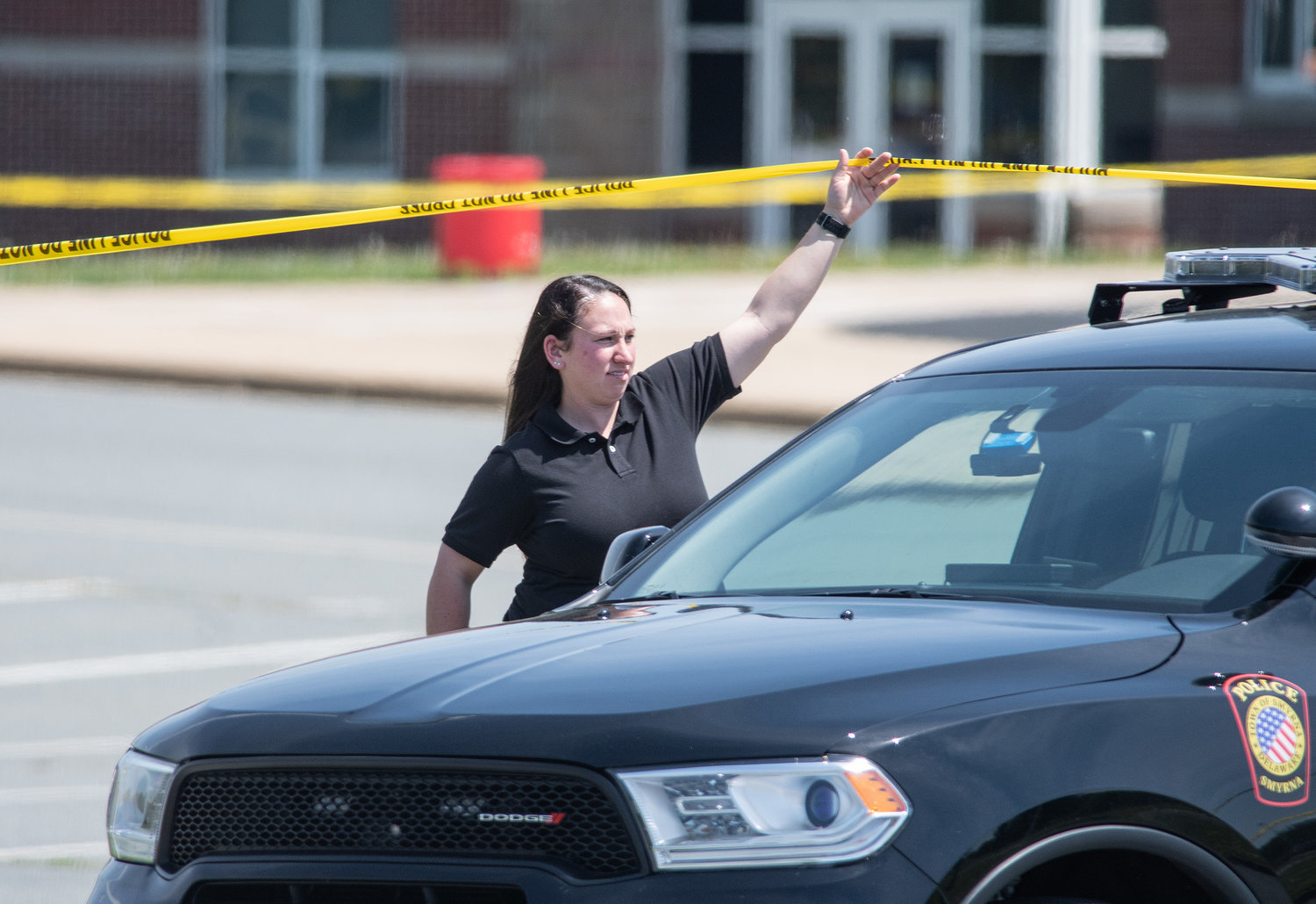 A Smyrna Police officer lifts caution tape as a police vehicle drives under it during a investigation of a murder of a women was shot and died in the front of the Middle School on Tuesday morning.