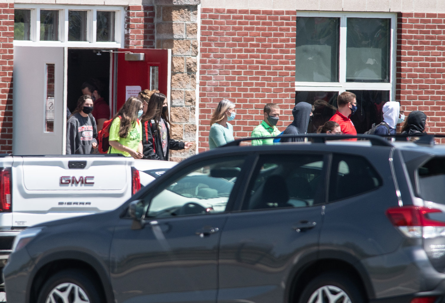 Smyrna Middle School students leave through a side door and head toward Smyrna High School to waiting buses and parents after a women was shot and died in the front of the Middle School on Tuesday morning.