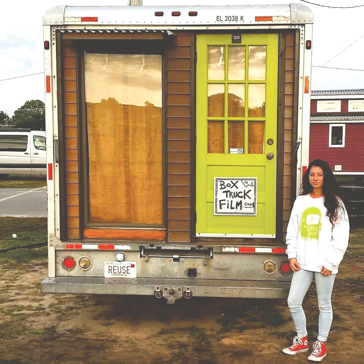 Aurora Robbins stands in front of Alex Eaves' upcycled tiny home.