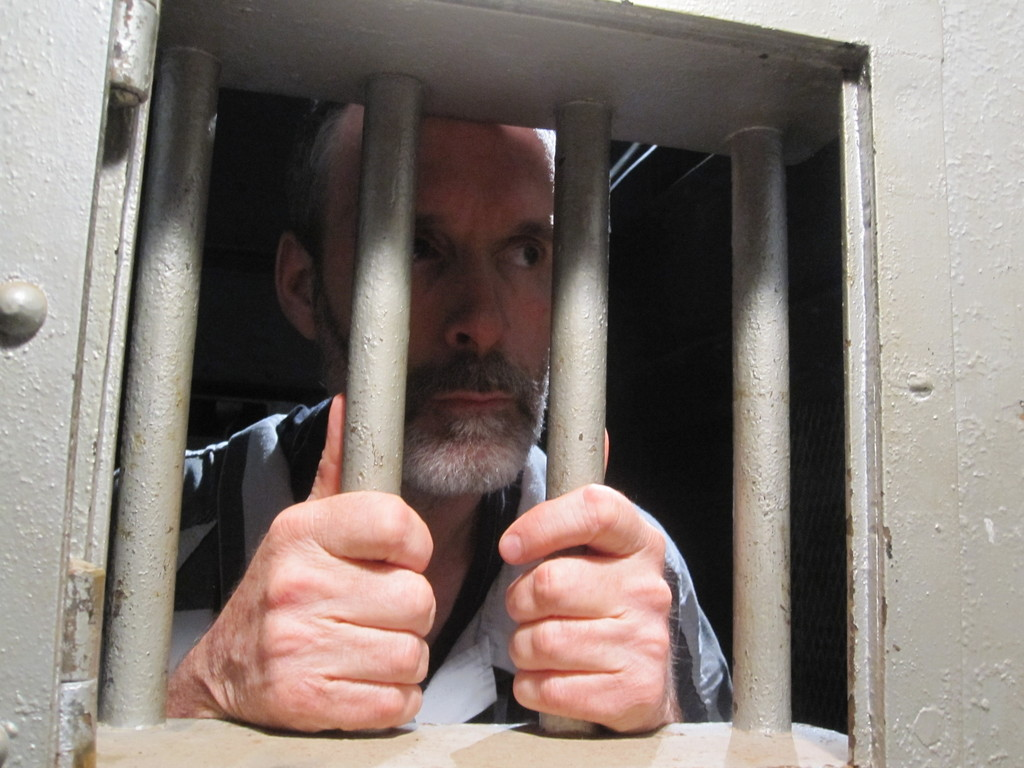 "Actor Paul Bathen peers from his prison cell in the old city jail at St. Marys City Hall during the filming of ""The Prisoner."""