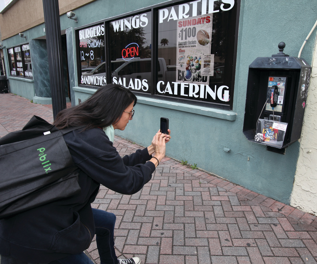 Yvonne Lozano photographs a calendar placed on an old pay phone on Edgewood Avenue in Murray Hill on a recent Free Art Friday. Lozano posts the images on several social media sites to give clues to the piece's whereabouts.