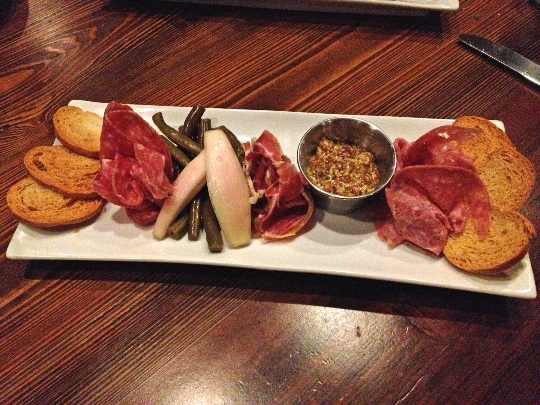 The charcuterie pairs toasted crostini with thin slices of dry-cured Serrano ham, soppressata and Genoa salami, tangy homemade pickled green beans and onions, and a spicy French Maille whole grain mustard.
