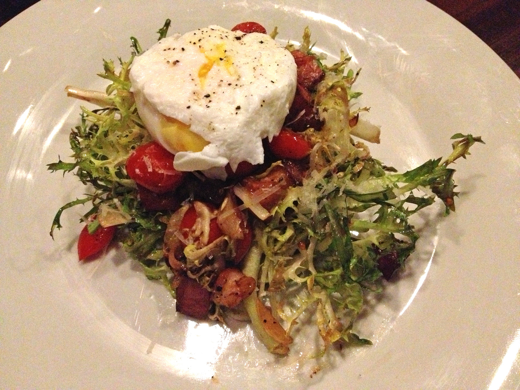 In this salad, the narrow curly pieces of frisée become lightly wilted by the oil in the warm bacon vinaigrette, and it's all topped with a perfectly poached, warm Black Hog Farm egg.