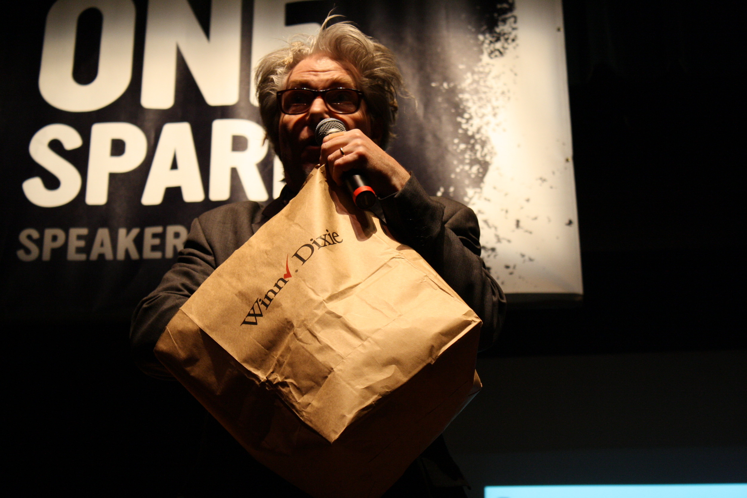 Martin Atkins throws blueberry muffins into the crowd at his One Spark Speaker Series talk.