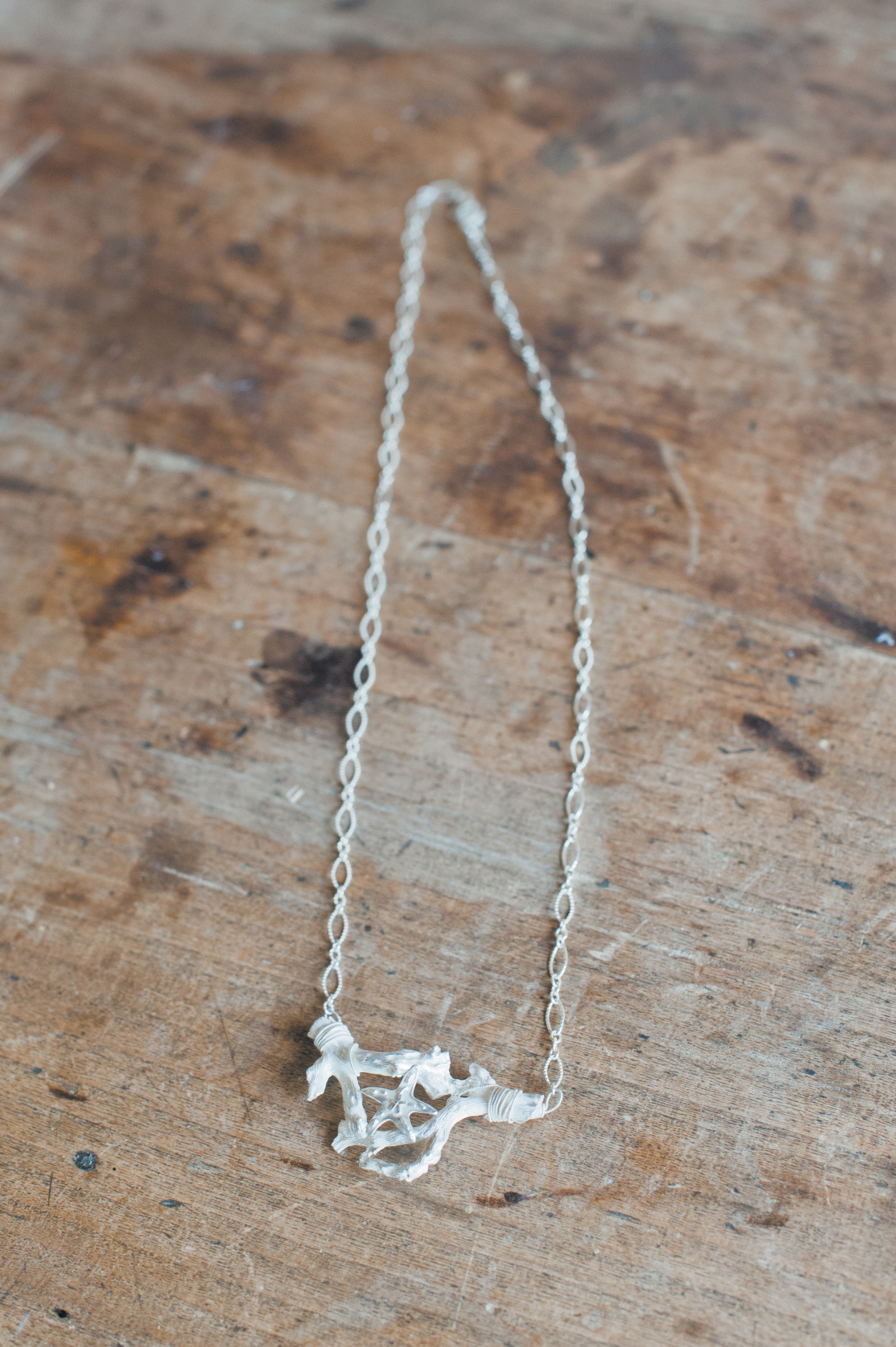 This necklace features a sterling silver casting of red Mediterranean coral with a small starfish.