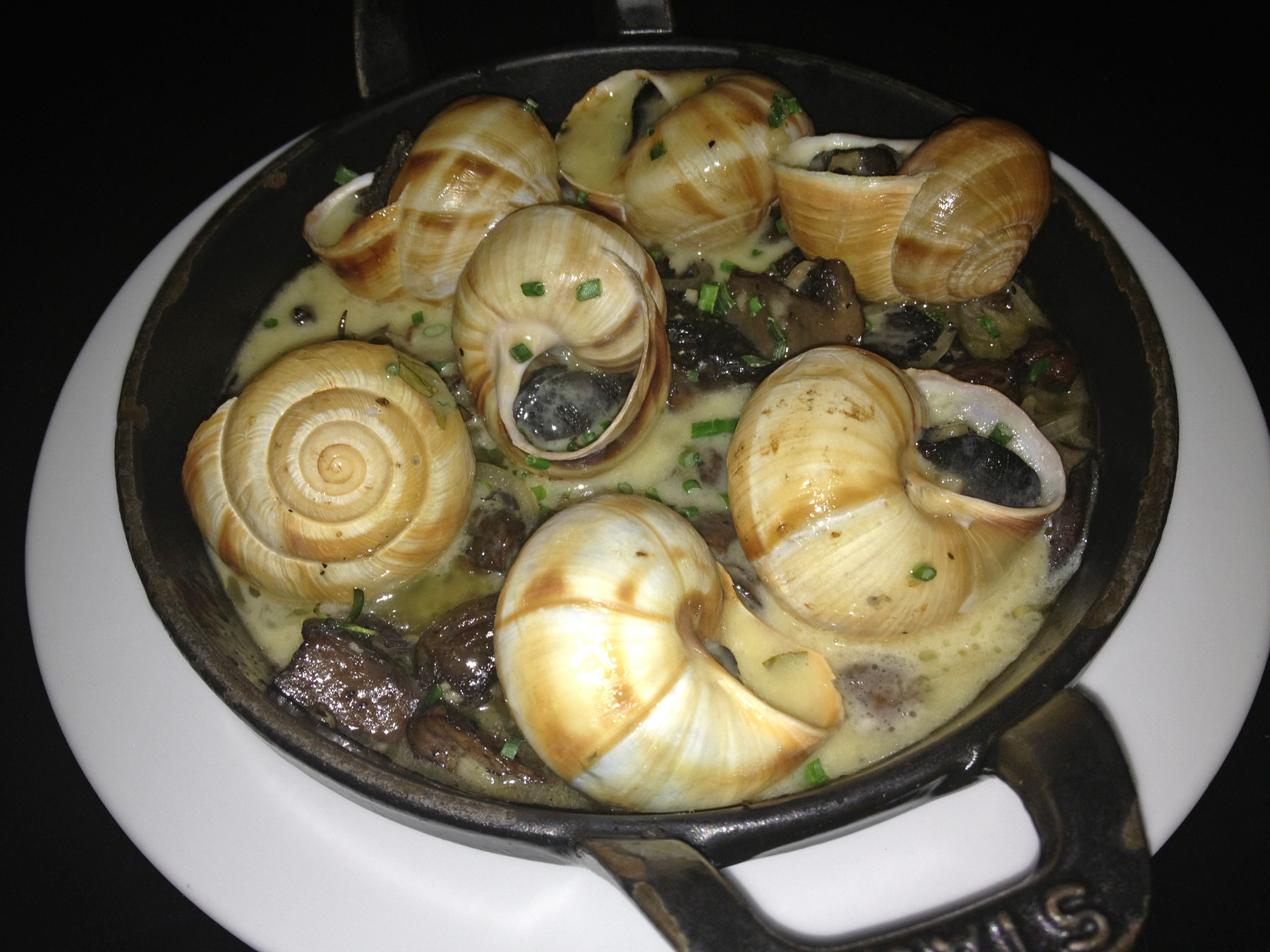 The escargots, with garlicky butter and thick, sautéed portobello mushroom slices, are a savory delicacy. They're served with local French Pantry crusty bread, perfect for sopping up the extra garlic butter.