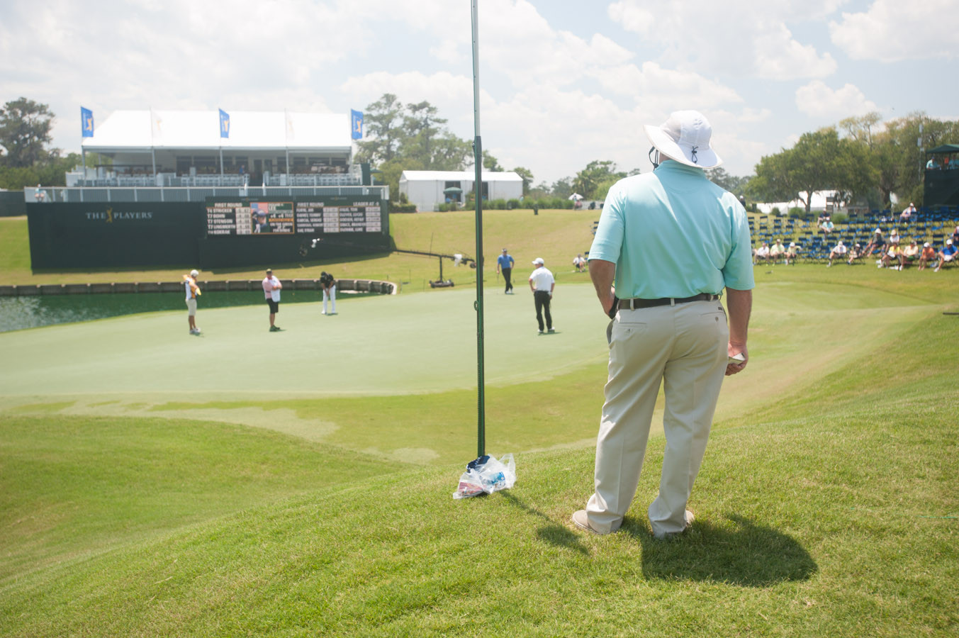 A tour volunteer watches James Driscoll take a practice putt on the 18th green.