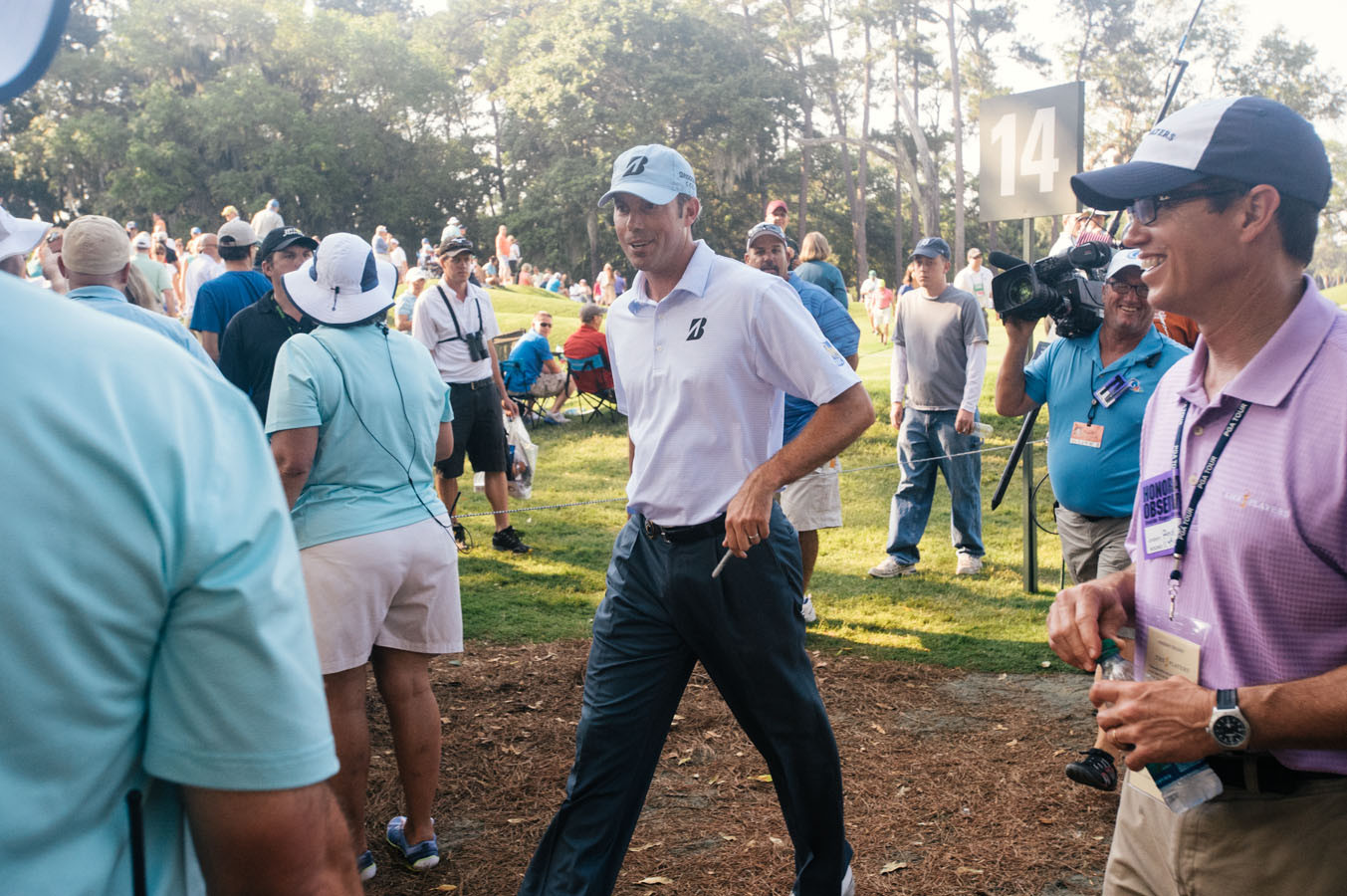 Matt Kuchar talks to volunteers as he walks towards the 15th tee.