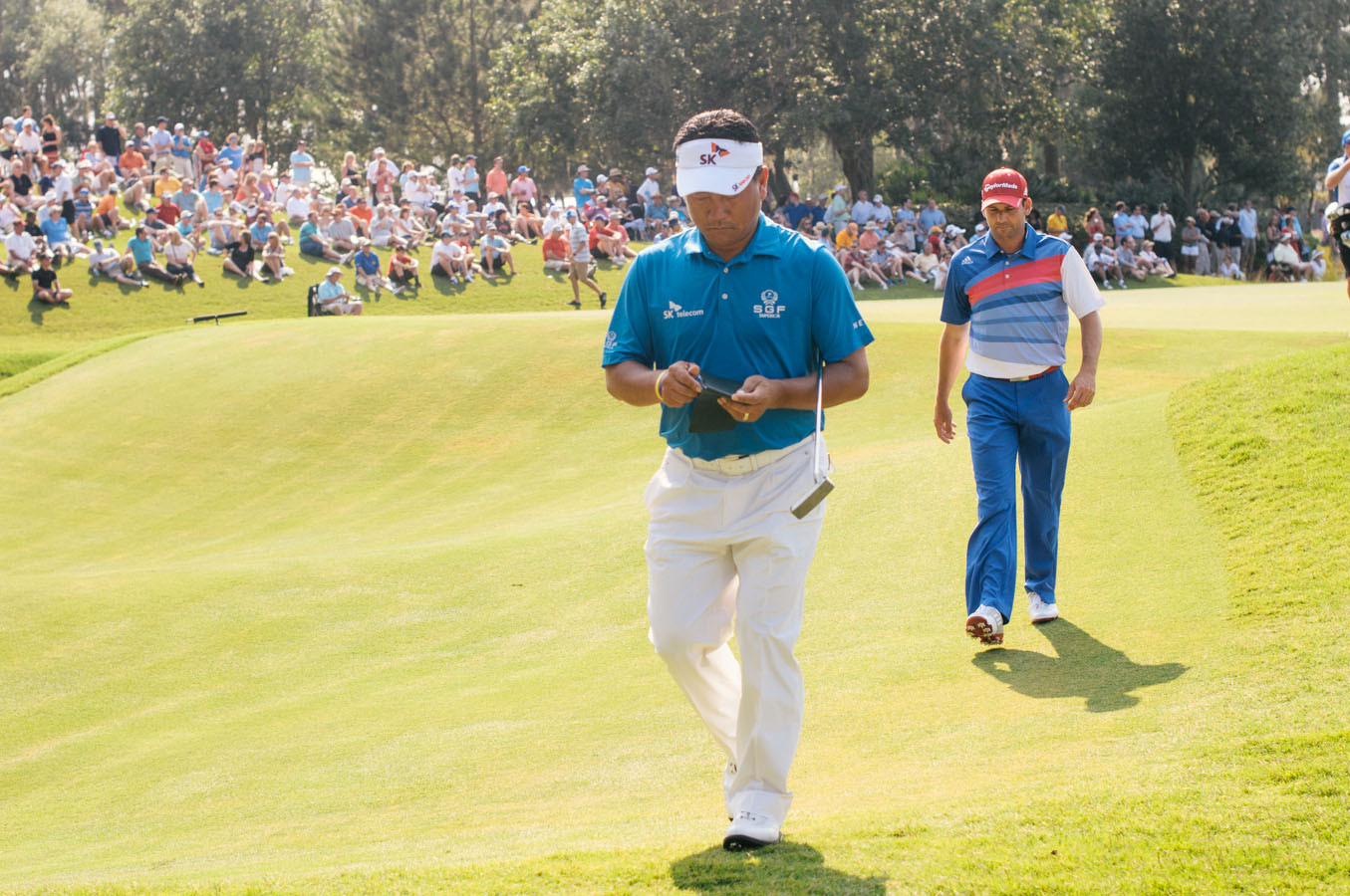 K.J. Choi and Sergio Garcia walk off the 16th hole.