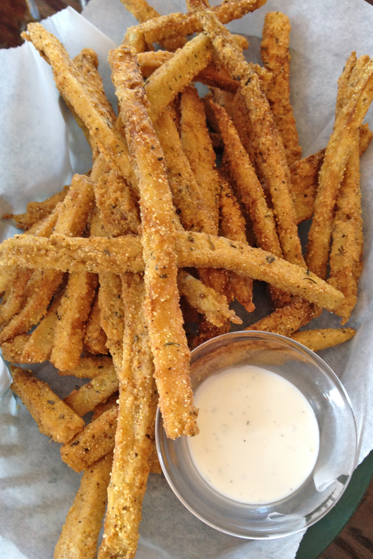 A heaping portion of thin, seasoned, cornmeal-dusted eggplant strips are served with a light homemade ranch dressing.