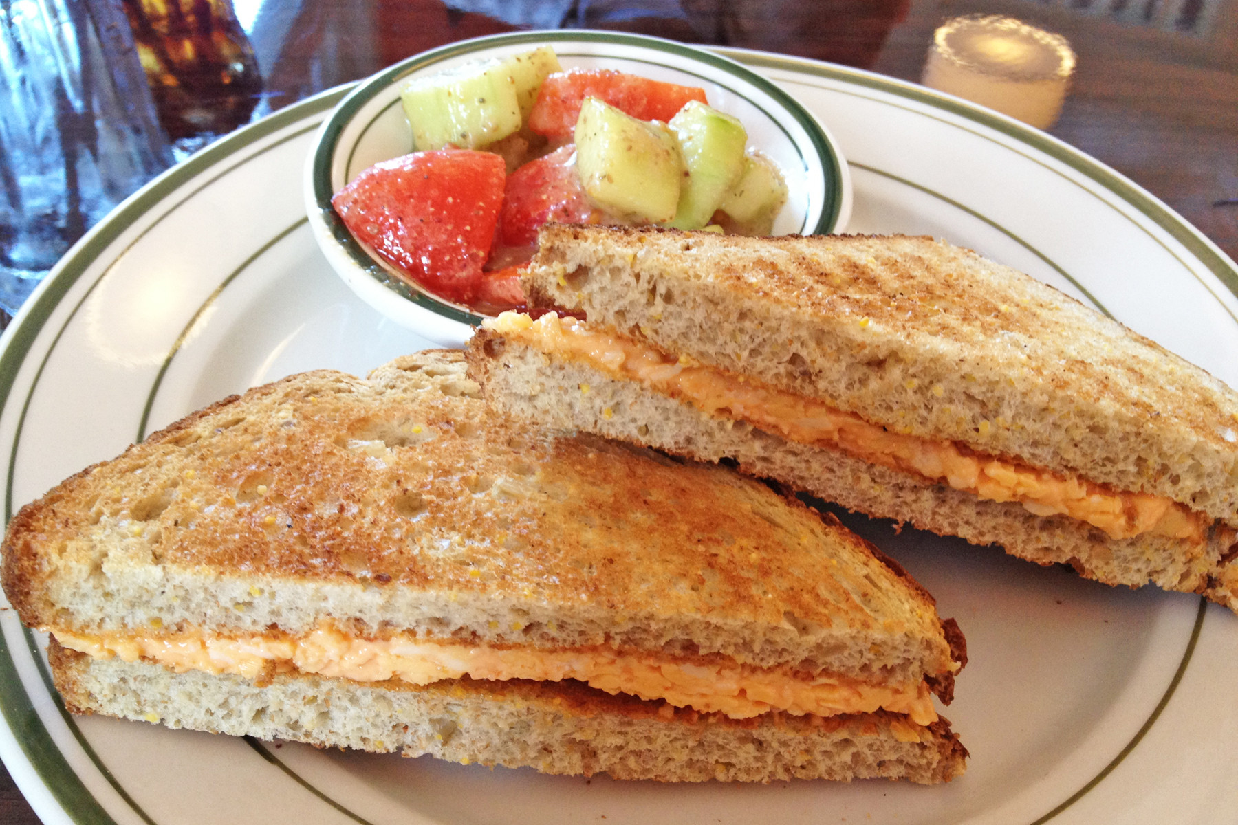 Creamy homemade pimento cheese on toasted multigrain bread with a side of cucumber and tomato salad is perfect for lunch or a light dinner.