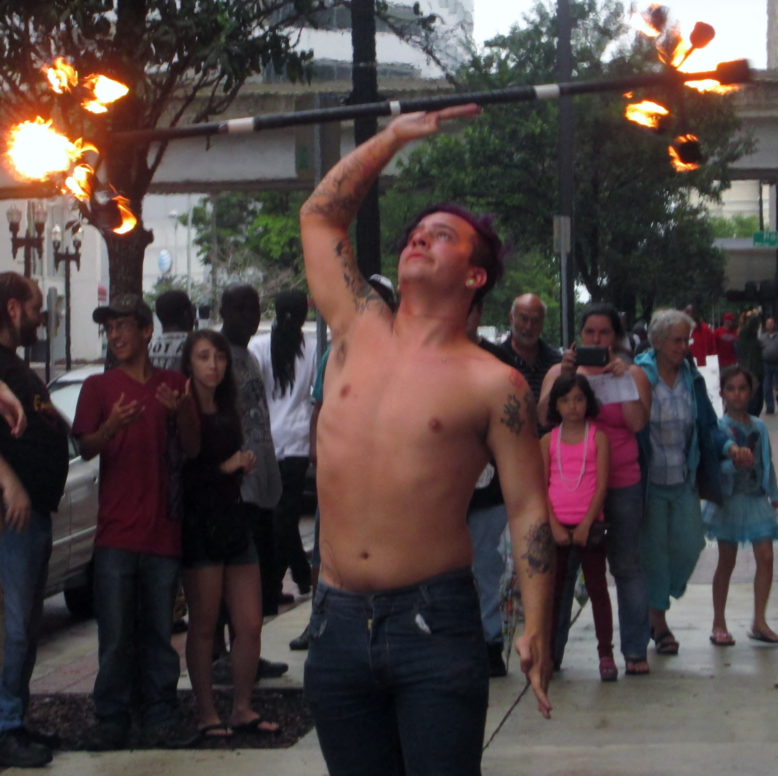 A man entertains the crowd with fire and his fancy moves.