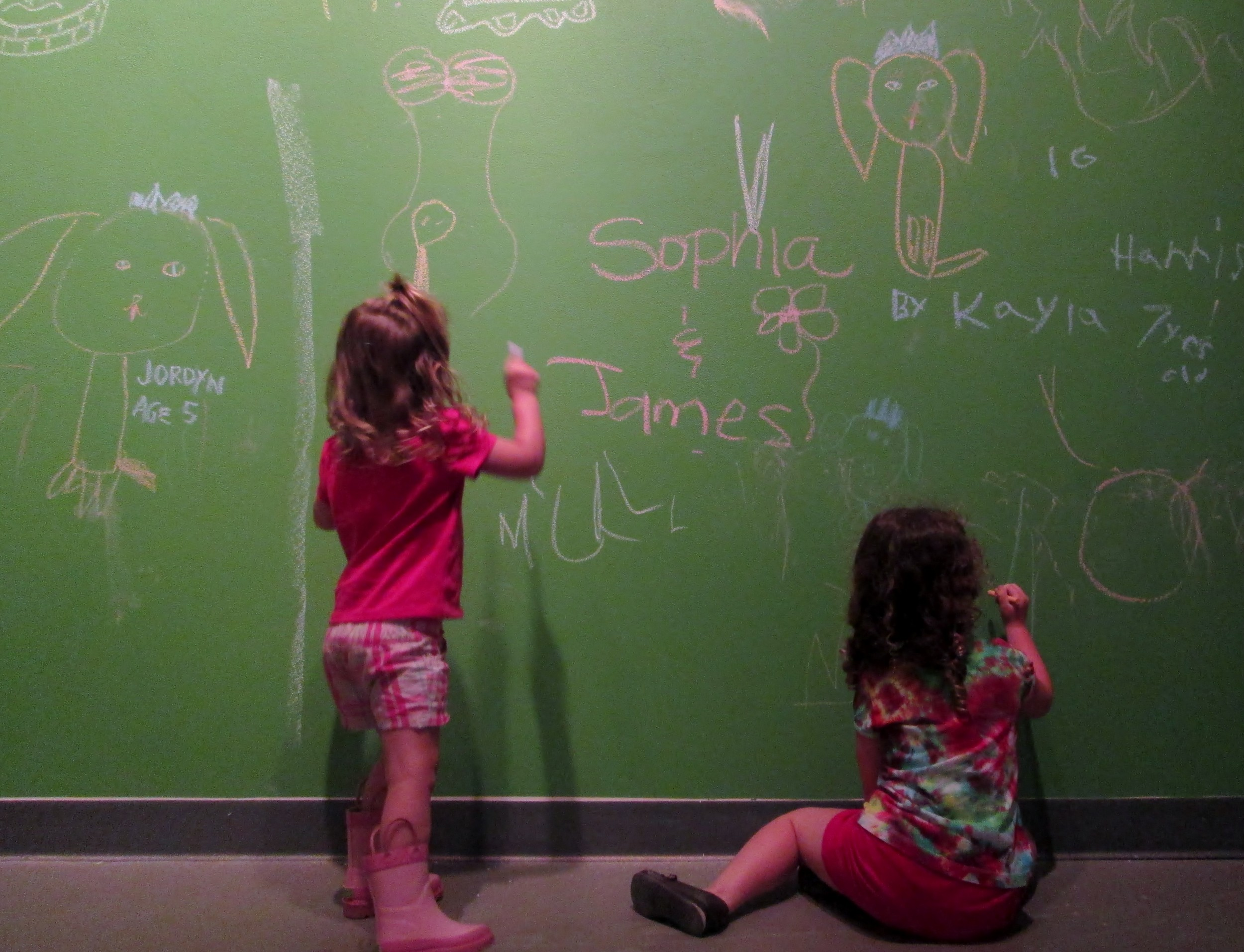 Riley and Megan create works of art on the Chalk It Up! walls of MOCA.