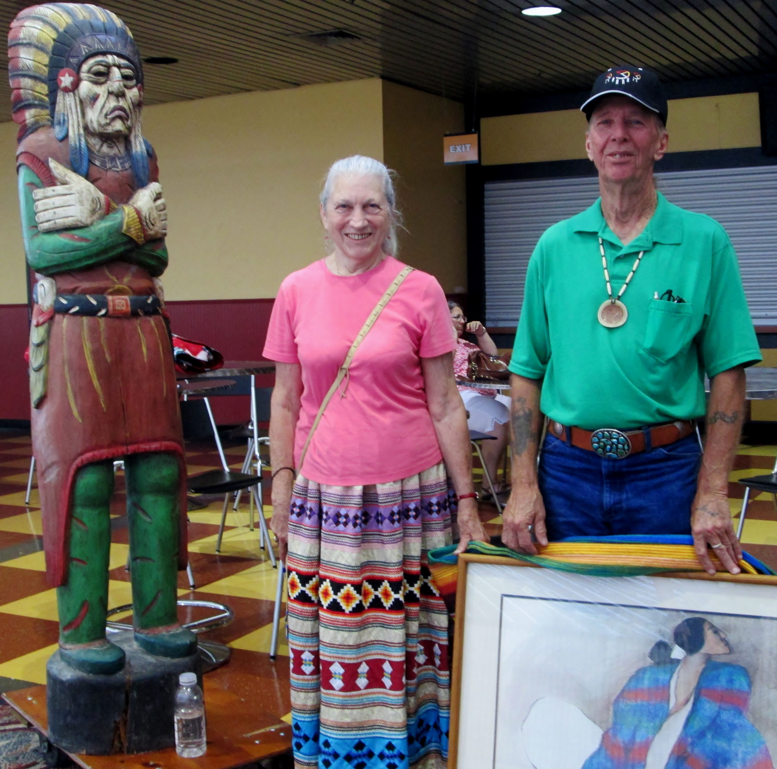 Mary Kent and Chi with their 1907 wooden carved Native American statue and painting
