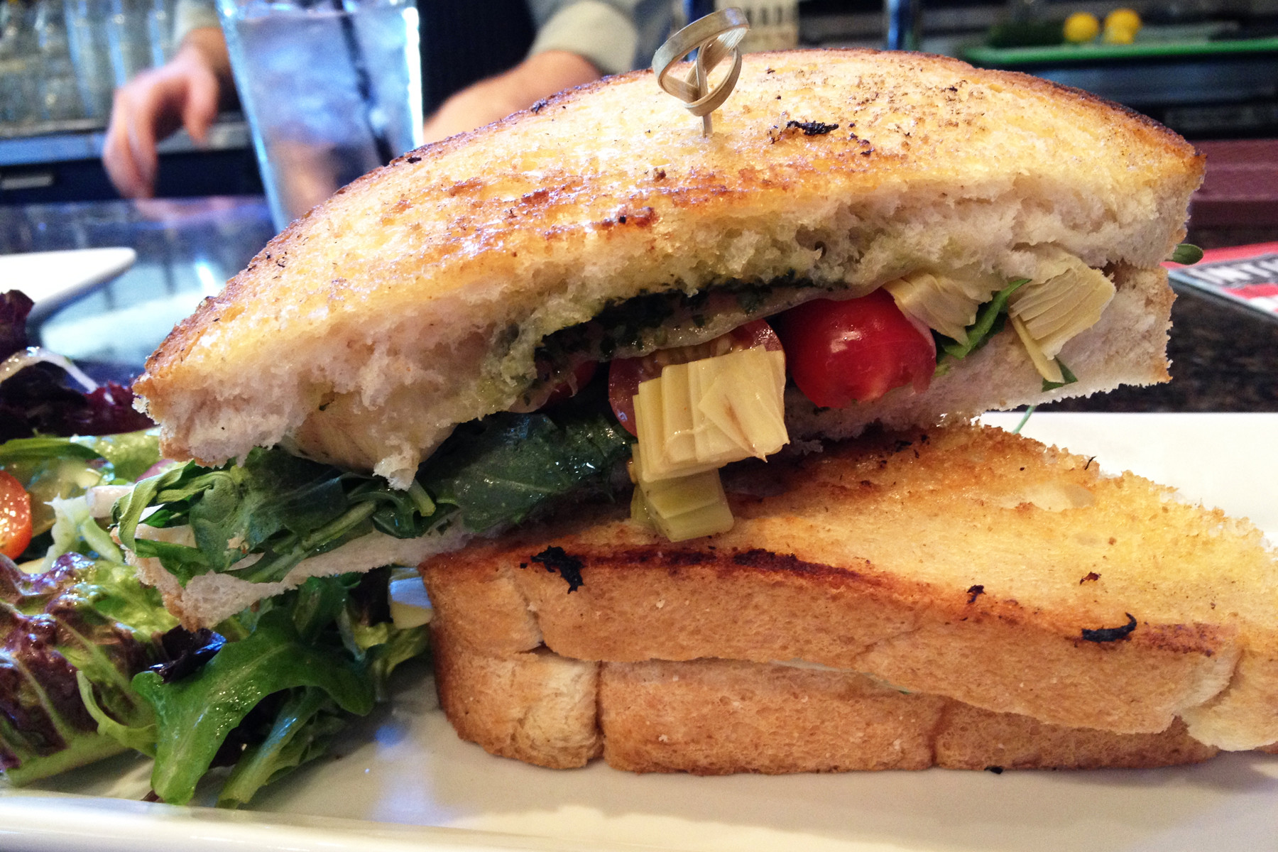 The Melt is slathered with basil pesto, artichoke hearts, grape tomatoes, peppery arugula and melted provolone pressed between two slices of buttered toast, accompanied by your choice of salad or fries.