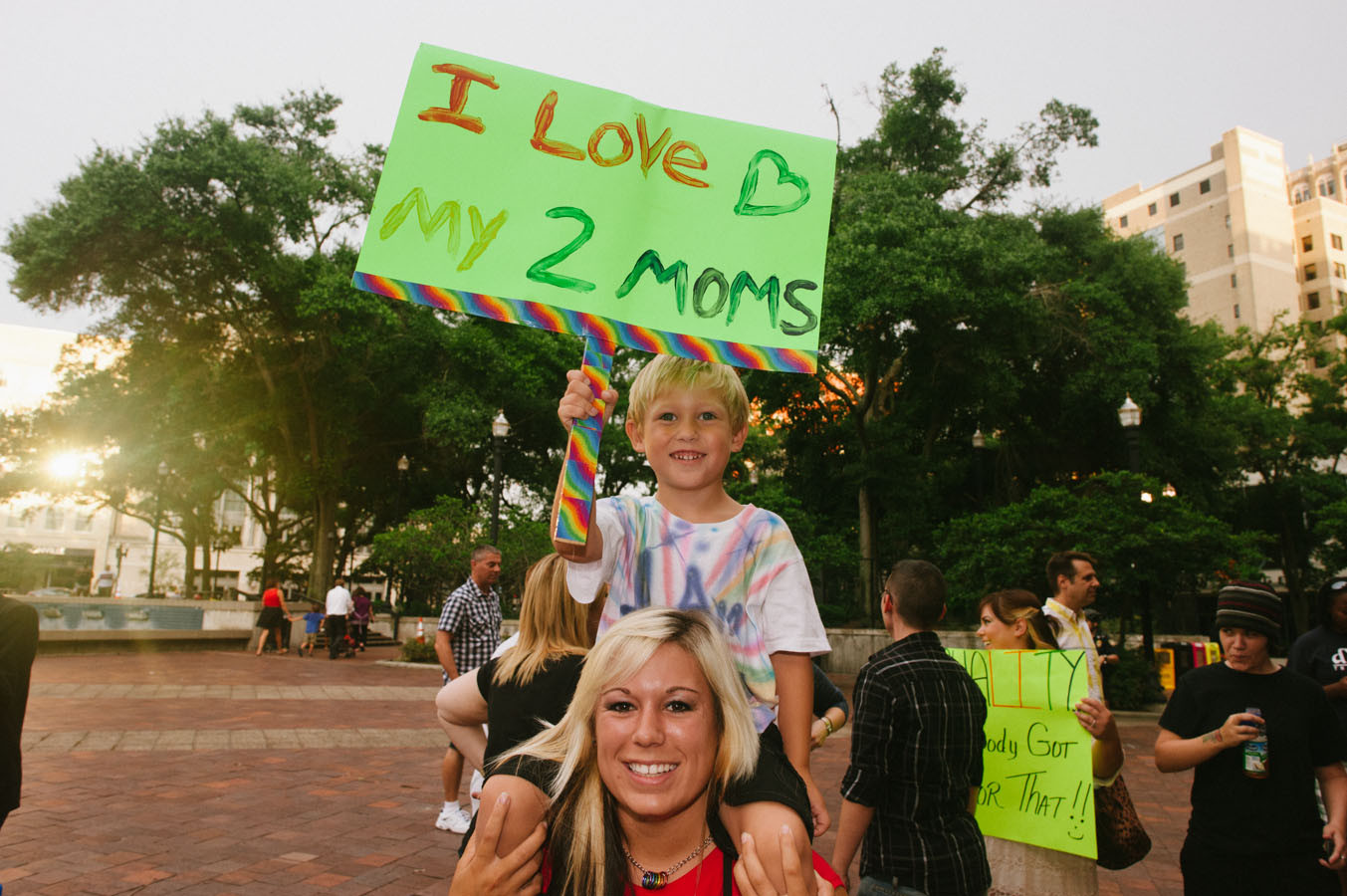 Kenny Cochran holds a sign extolling his love for his two mothers while sitting on his Aunt Jessi Minsch's shoulders.