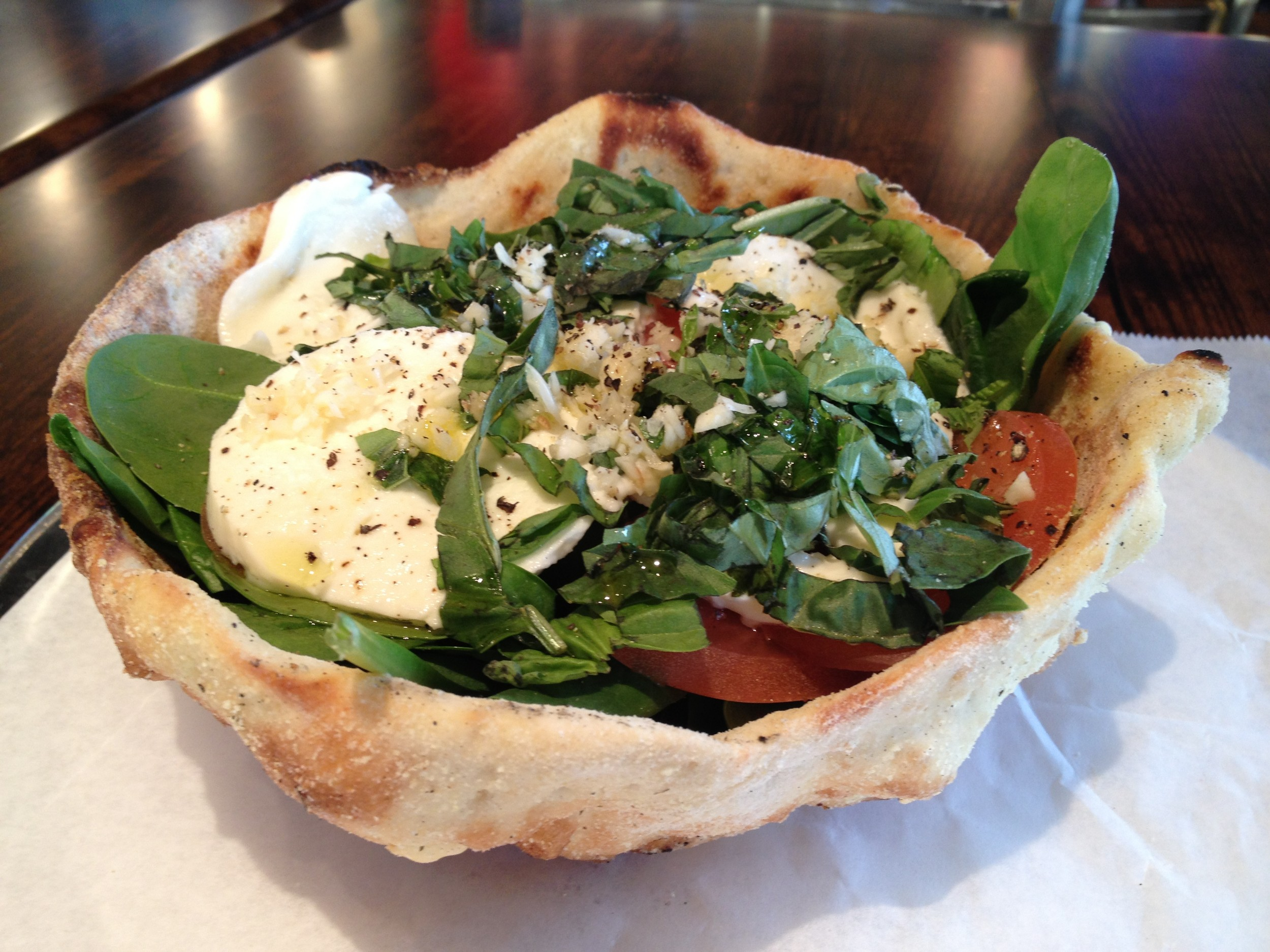 The caprese salad is filled with slices of fresh mozzarella, leafy spinach, tomatoes and shredded basil with extra virgin olive oil and a side of balsamic dressing, served in a baked pizza-dough bowl.