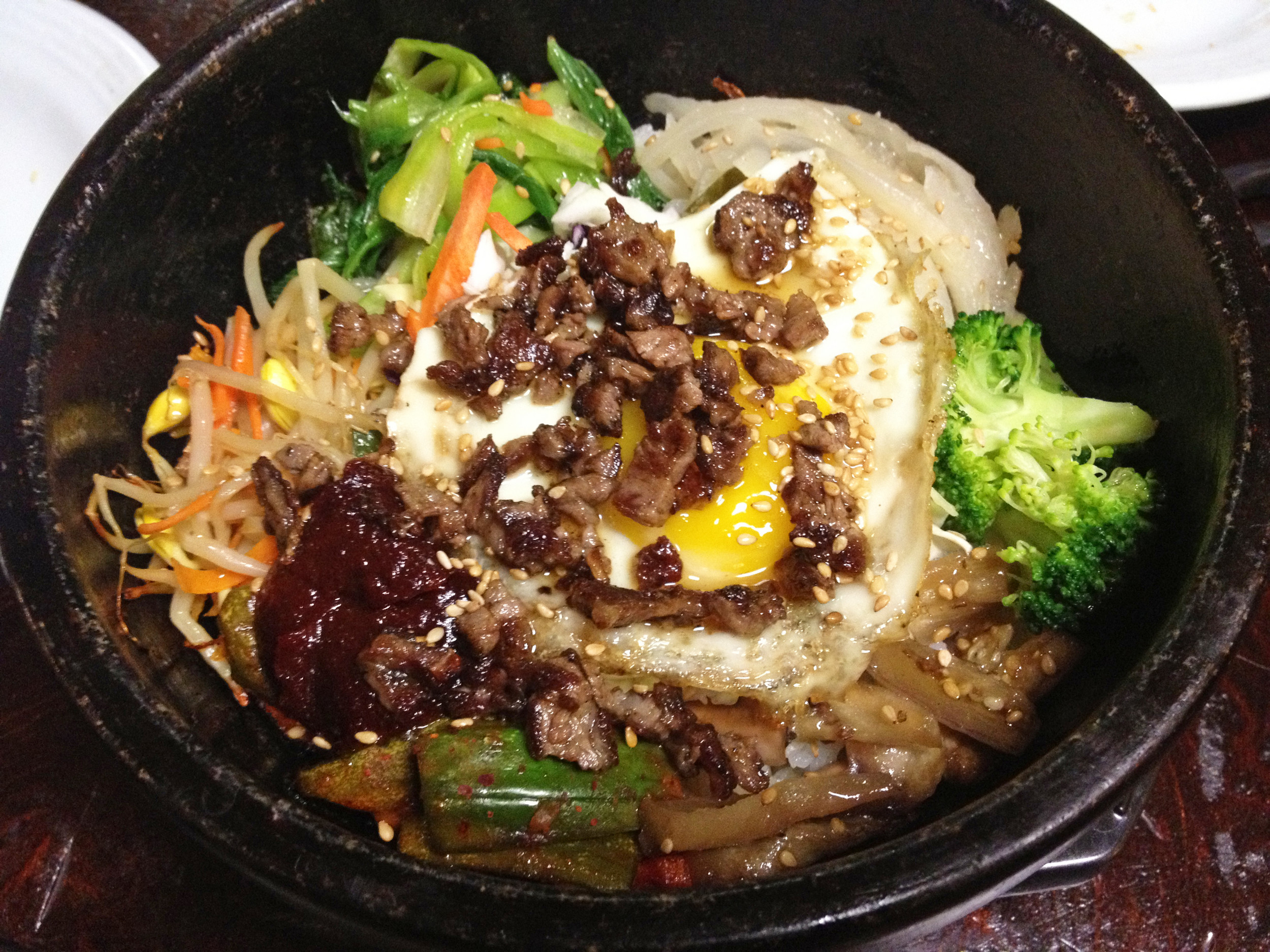 "The bibimbap at Hon Korean is a ""mixed rice"" dish that comes with an assortment of vegetables and a raw egg that cooks when you break it in the piping hot stone pot, called a dolsot"