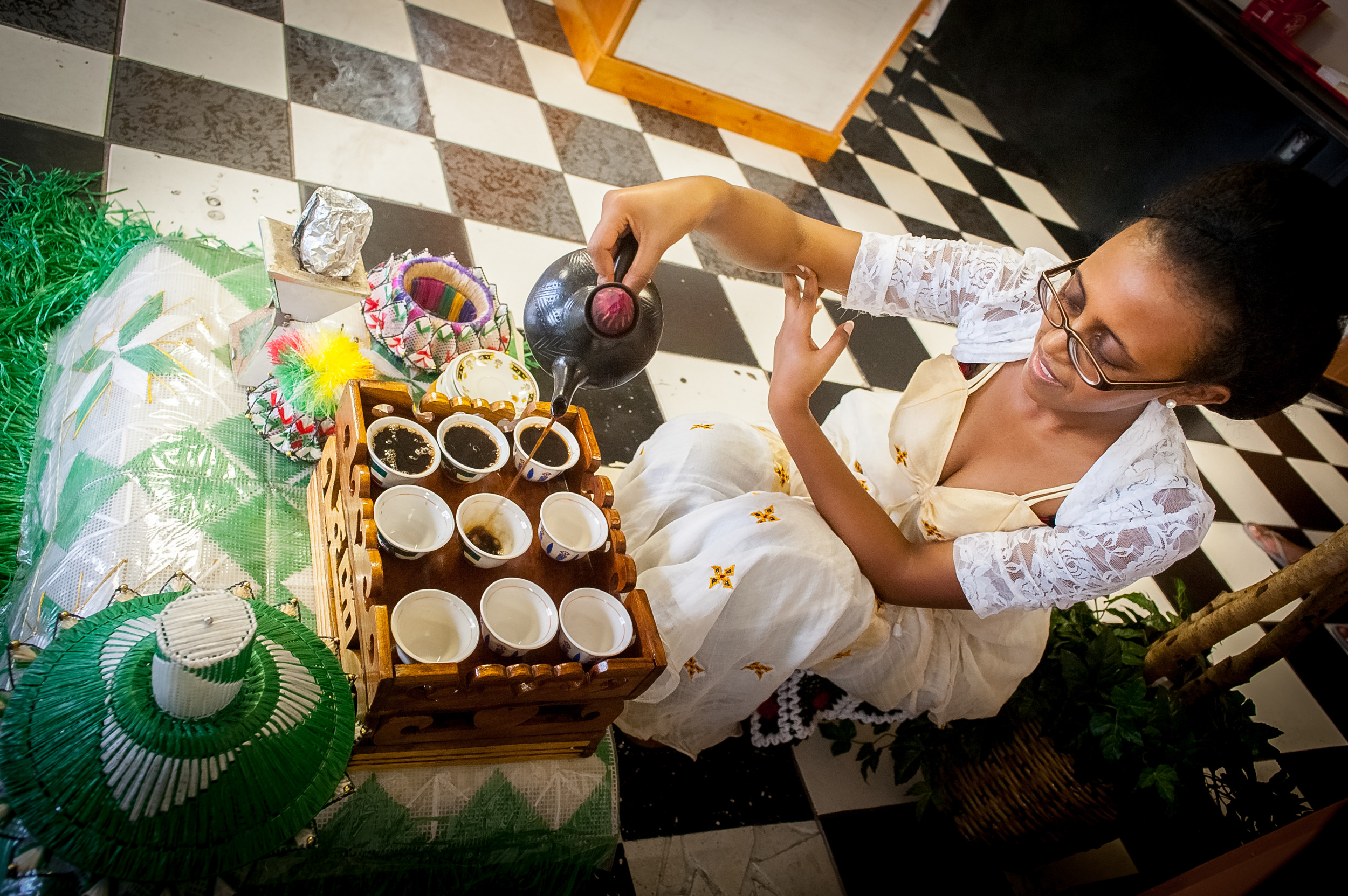 During the ritual coffee ceremony, Hiwot Mideksa pours everyone a cup, bringing out sugar, salt and accompanying snacks such as a bowl of popcorn. Photos: Fran Ruchalski