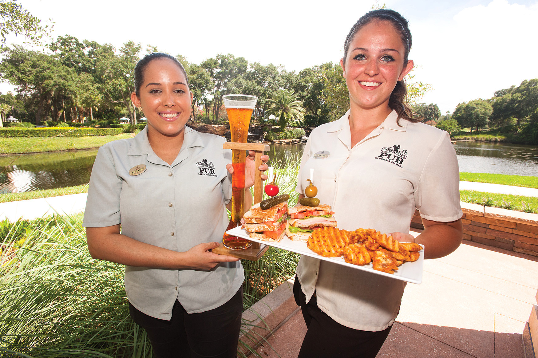 Melody Rodriguez Burgos and Taylor Drury of Alice & Pete's Pub inside Sawgrass Marriott Golf Resort & Spa in Ponte Vedra present a yard of Intuition People's Pale Ale and Pete's Designer club sandwich with ham, turkey, Swiss, cheddar, bacon, lettuce and tomato.