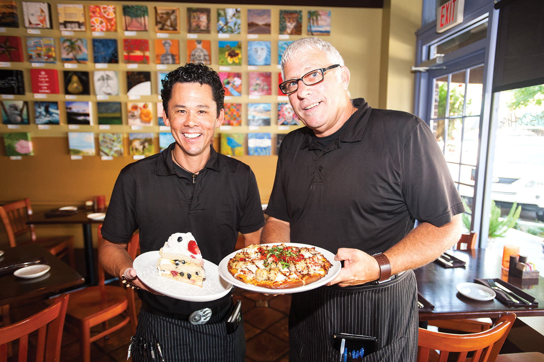 Biscottis servers Danny Stimson and Steve Pulsifer show off the mixed berry custard cake and the artichoke and prosciutto pizza in Avondale.