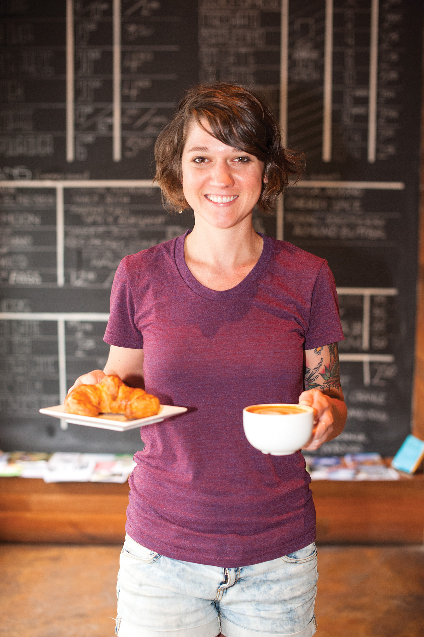 Barista Claire Sommers Buck at Riverside's Bold Bean Coffee shows off a croissant and latte.
