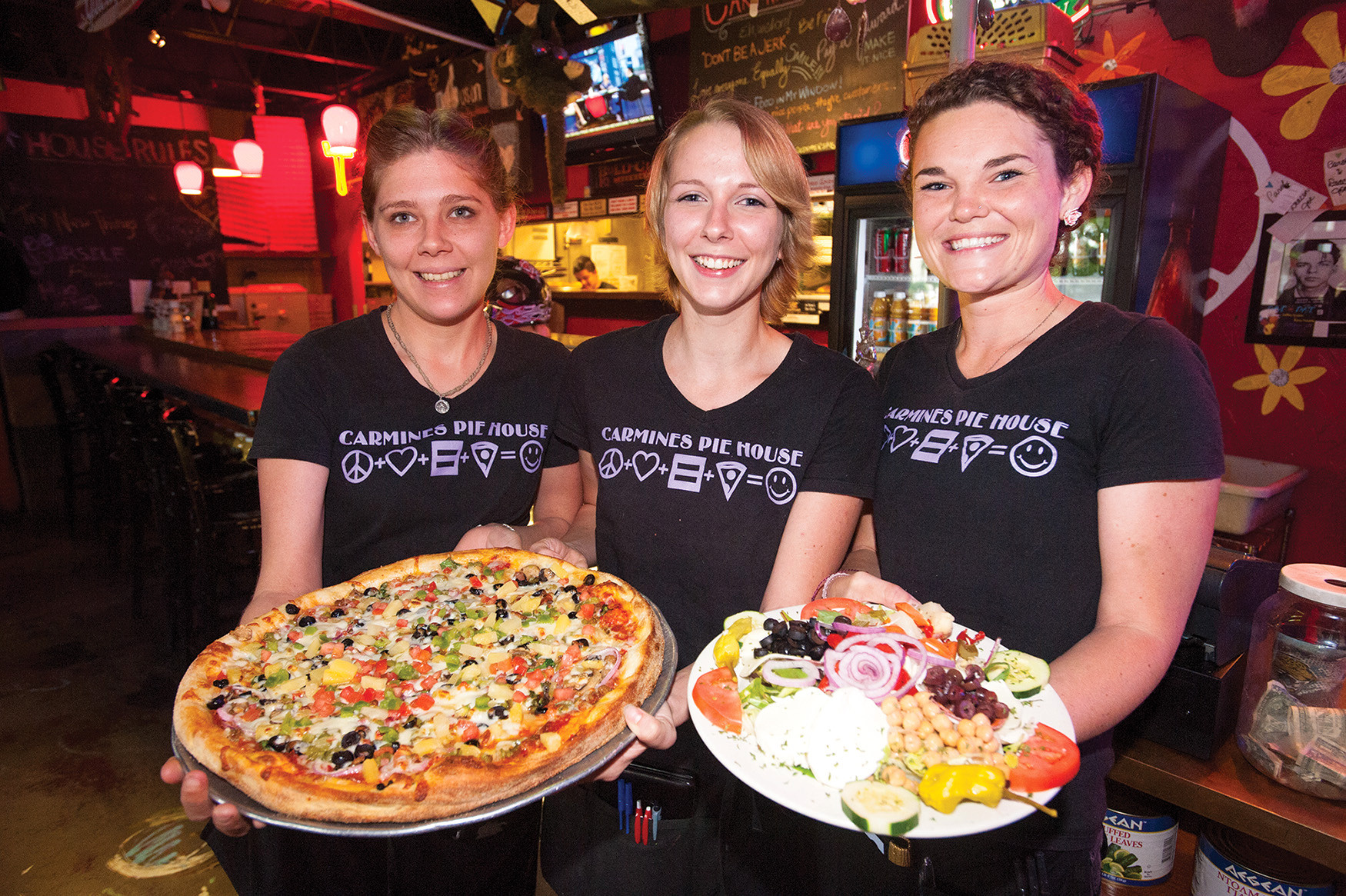 Isis Gaugler, LaRissa Bruce and Sarah Brown of Carmine's Pie House present their signature Train Wreck pizza and Carmine's salad in Riverside.