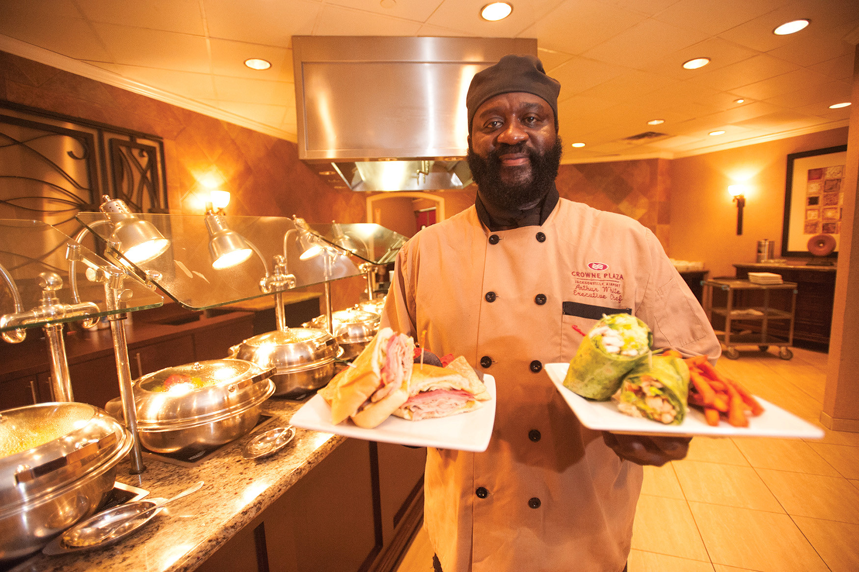Chef Arthur White of Savannah Bistro inside the Crowne Plaza near the airport shows off the buffet and a pressed Cuban sandwich and turkey wrap with sweet potato fries.