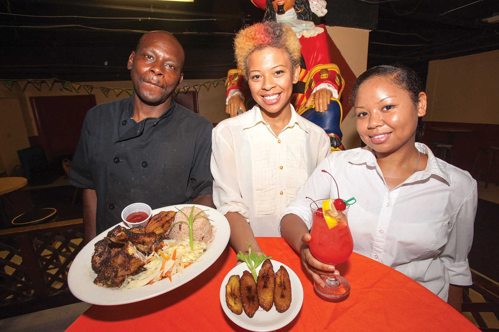 Chef Richard Powell, Christine Harris and Mimi Prejean of Da Real Ting Café Downtown present their signature jerk chicken with beans and rice, a plate of fried plantains and a glass of rum punch.