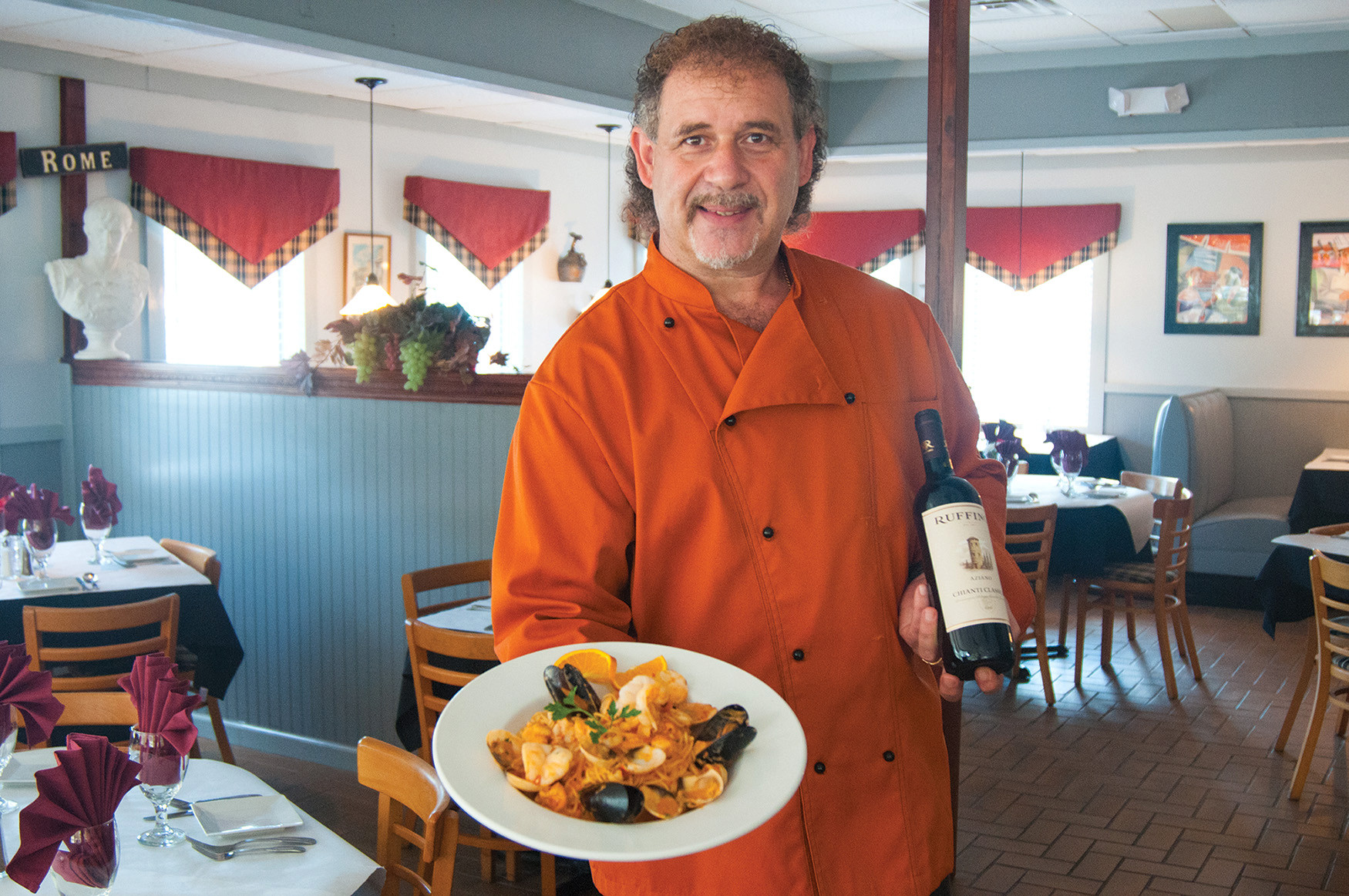 Executive Chef and Owner Tonino Di Bella of Mangia Italian Bistro & Bar on St. Johns Bluff Road South holds a plate of spaghetti amalfi with chopped fish, clams, mussels and shrimp over pasta in a creamy marinara sauce.