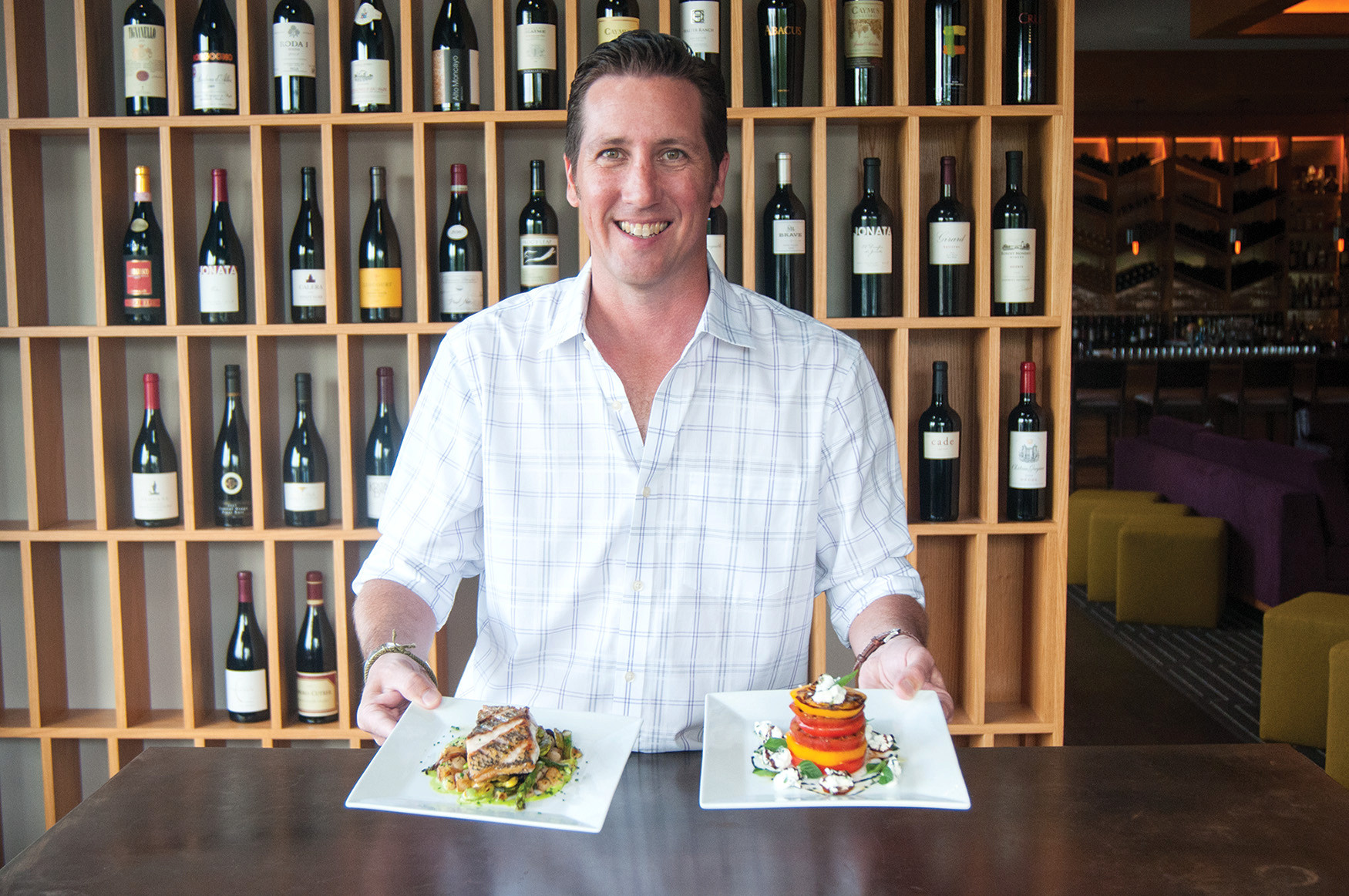 Managing Partner Chad Munsey of Ovinté in St. Johns Town Center presents a plate of the Il Pesce Di Ovinté (left) and an heirloom tomato salad.