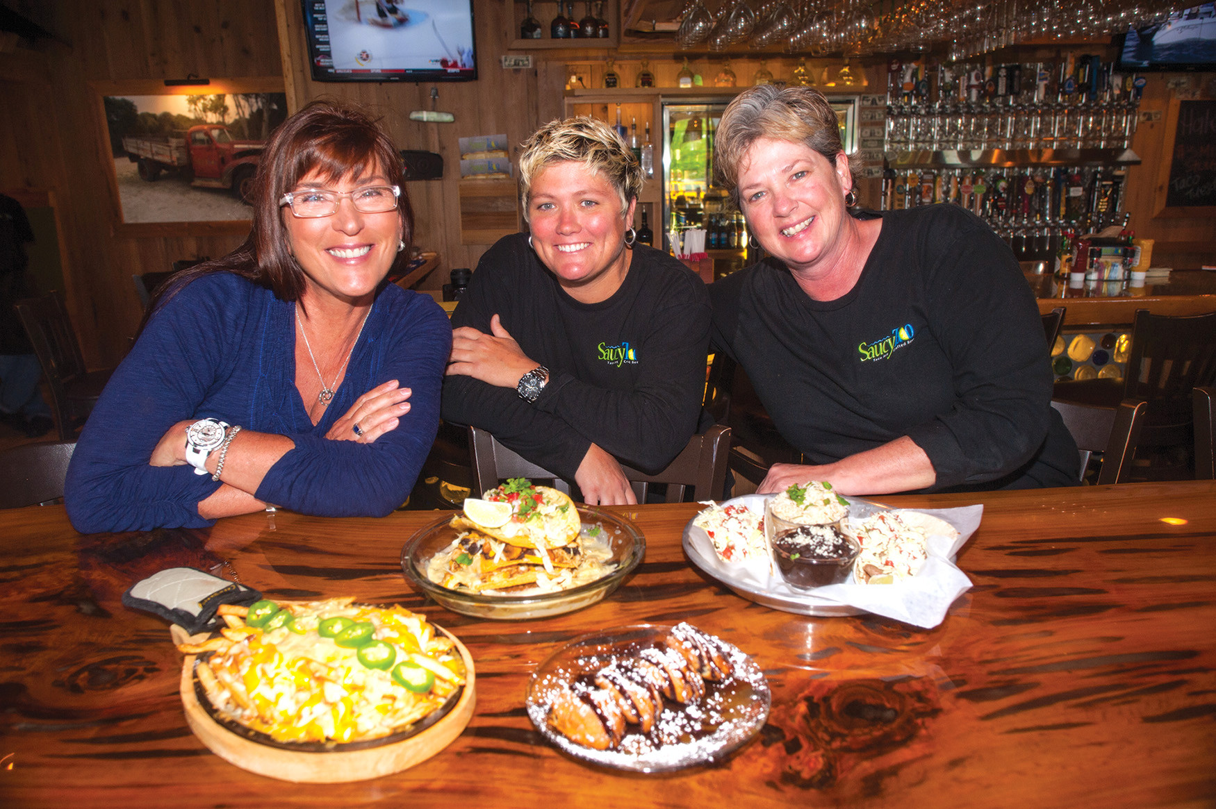 Owners Kristi Kluba, Allison O'Connor and Bonnie Turk of Saucy Taco in St. Johns introduce a wide selection including the Saucy Fries (left), tostada, fried Oreos and the Saucy Taco.