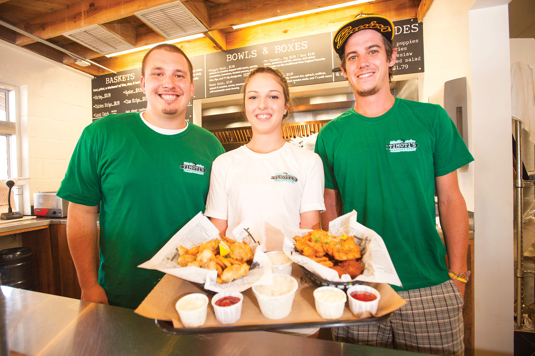 Joey Monty, Destiny Browning and Shane McNeil of Timoti's Seafood Fry Shak in Fernandina Beach display combo baskets of fried shrimp, fried oysters and the catch of the day.
