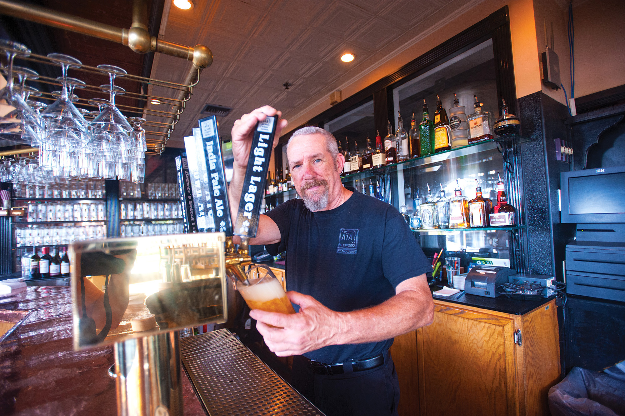 Dale Lloyd, A1A Ale Works' long-time bartender, pours a King Street Light Lager, perfect after a hot day in the Oldest City.