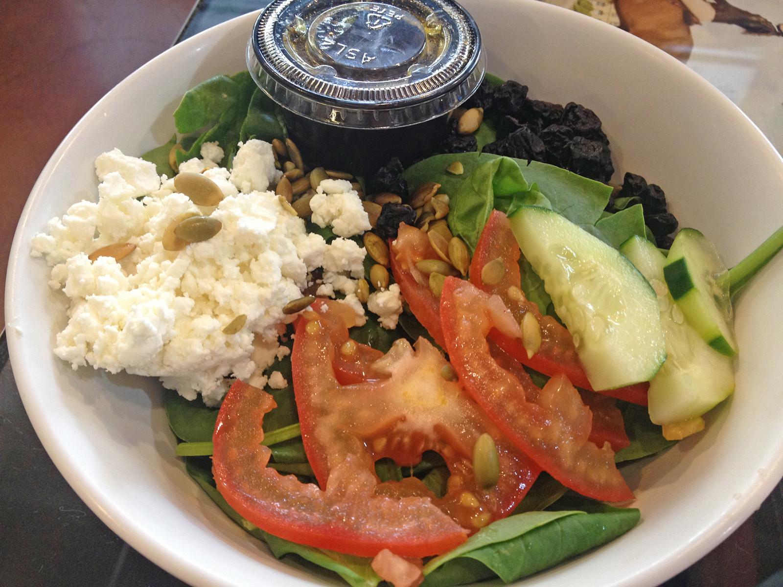The goat cheese half-salad is fresh spinach topped with creamy goat cheese, dried sweet blueberries, crunchy pepitas (raw pumpkin seeds), tomatoes and cucumbers, and accompanied by balsamic vinaigrette.