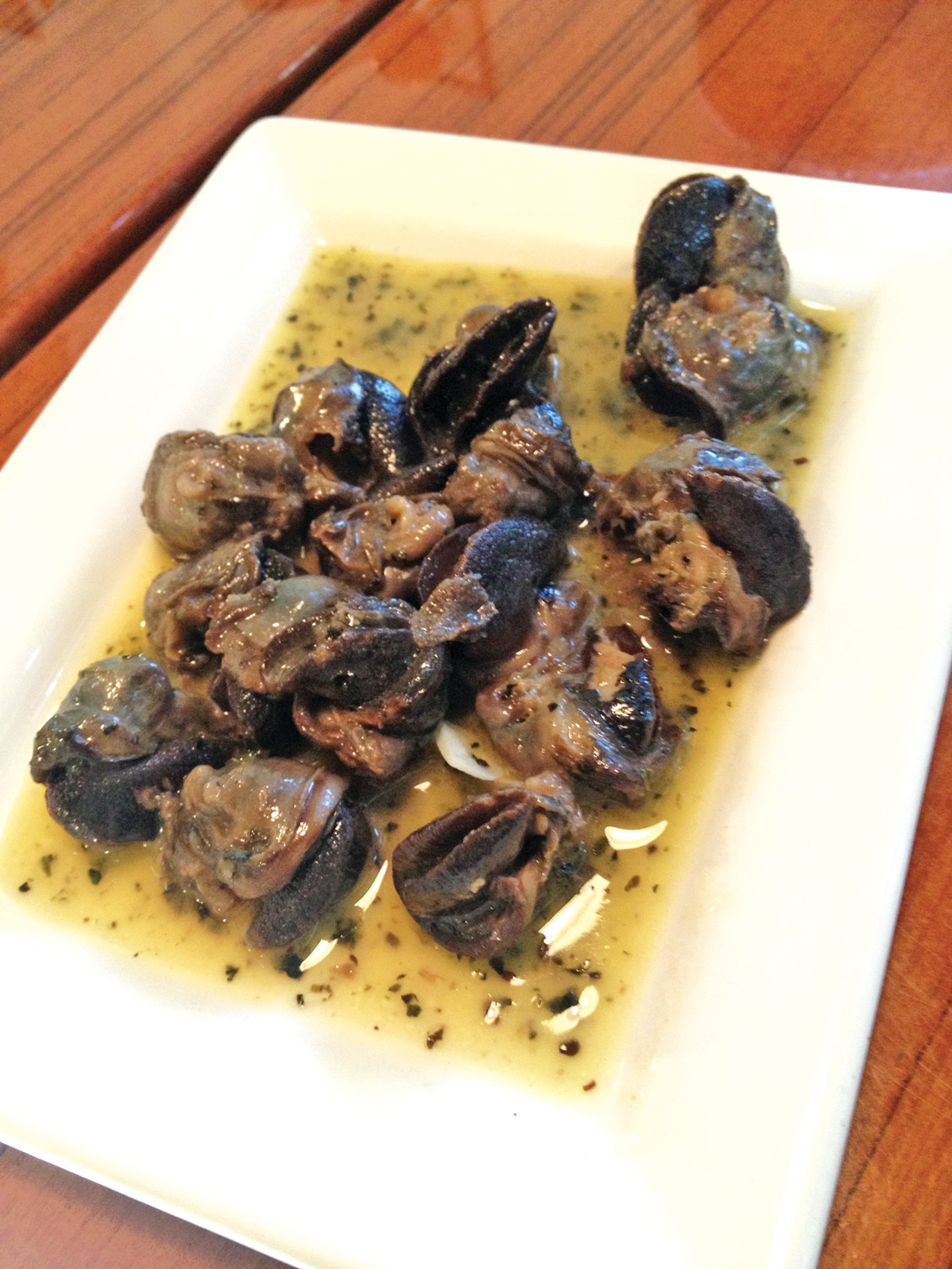 The escargot (snails) are served with a sweet basil and garlicky butter sauce.