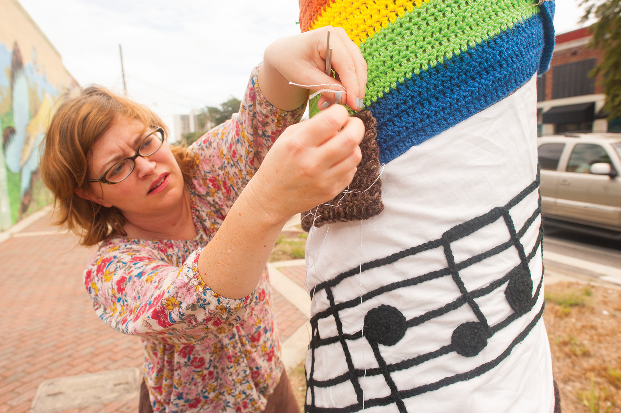 "Yarn Bomb Jax artist Lenai Waite installs a rainbow piece with musical notes from ""Somewhere Over the Rainbow"" in Five Points.  Photos: Dennis Ho"