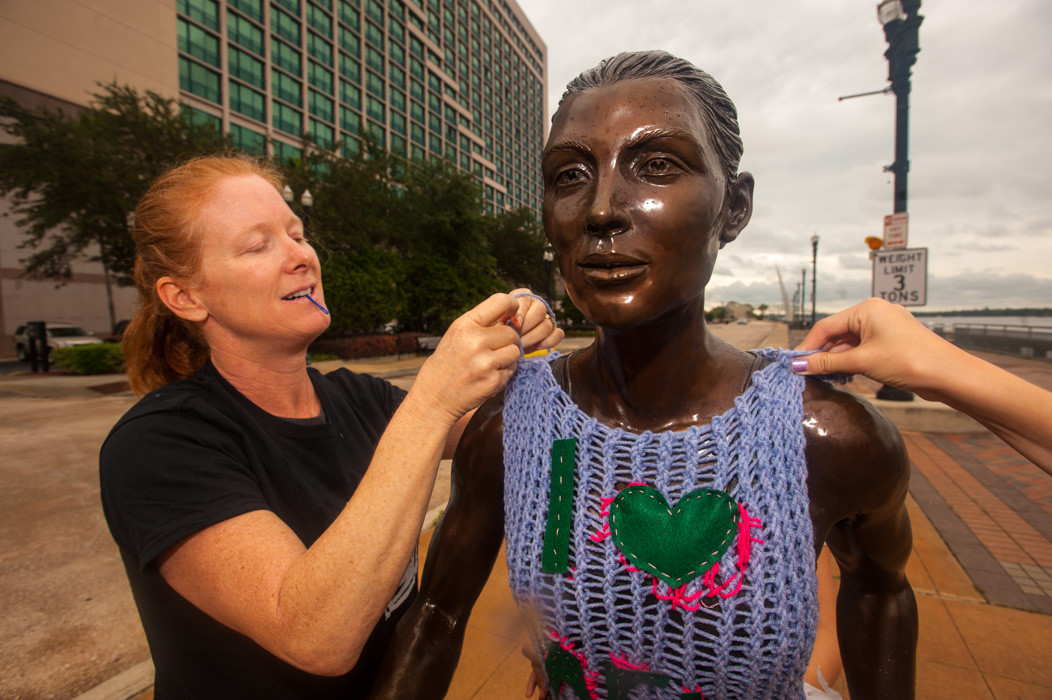 Patricia Bausch installs her yarn bomb on the river walk.